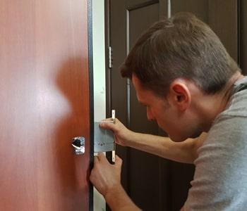Мастер врезает замок в дверь